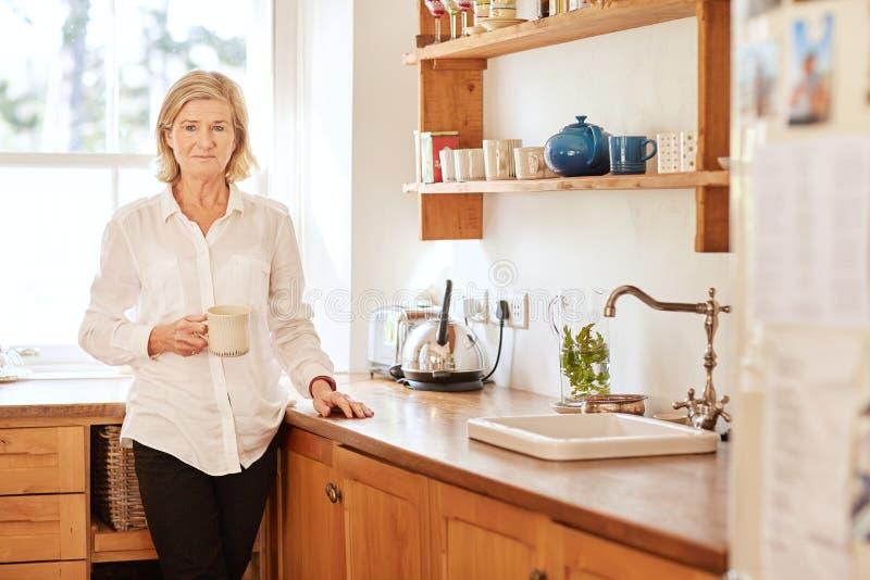 Bekymrat seende högt kvinnaanseende i hennes kök arkivbild