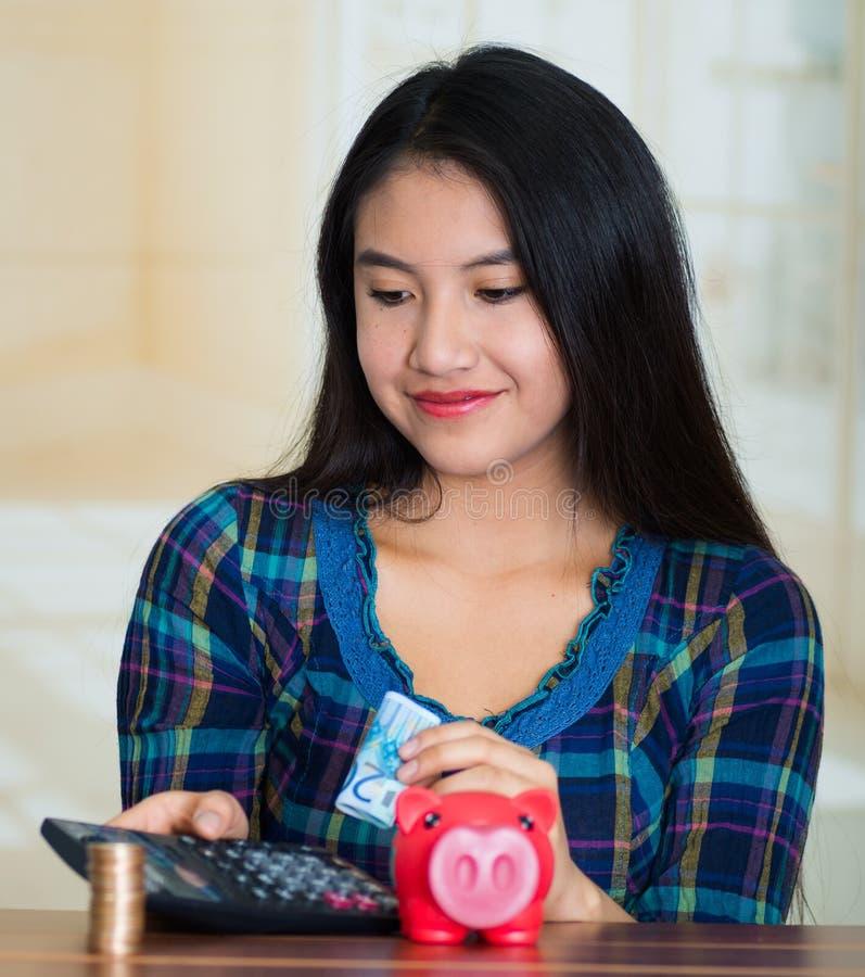 Belägen mitt emot kamera för ung brunettkvinna, hållande pengarräkningar och räknemaskin, ett spargrissammanträde på tabellen bre arkivbilder
