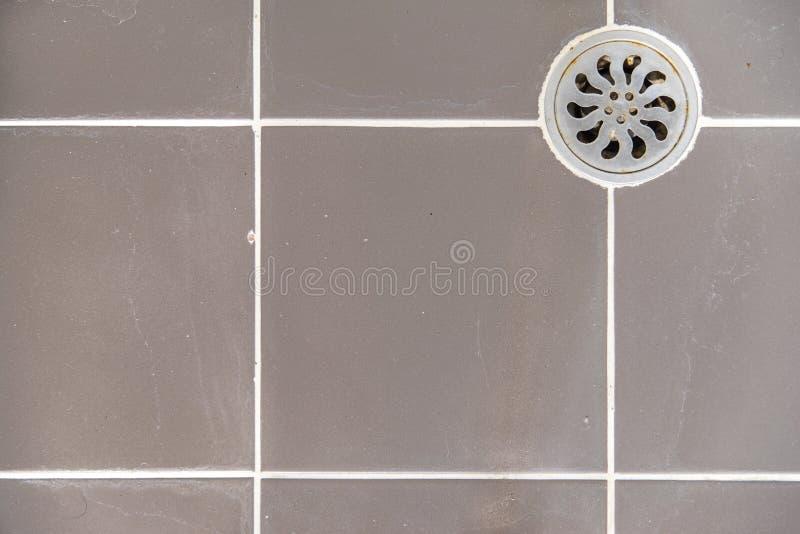 Belägga med metall avrinninghålet i det smutsiga belade med tegel golvet royaltyfria bilder
