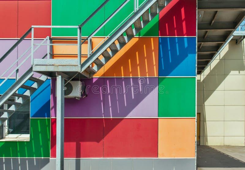 Belägga med metall brandflykten eller den nöd- utgången på den mångfärgade väggen av byggnad, abstrakt stads- bakgrund royaltyfria foton