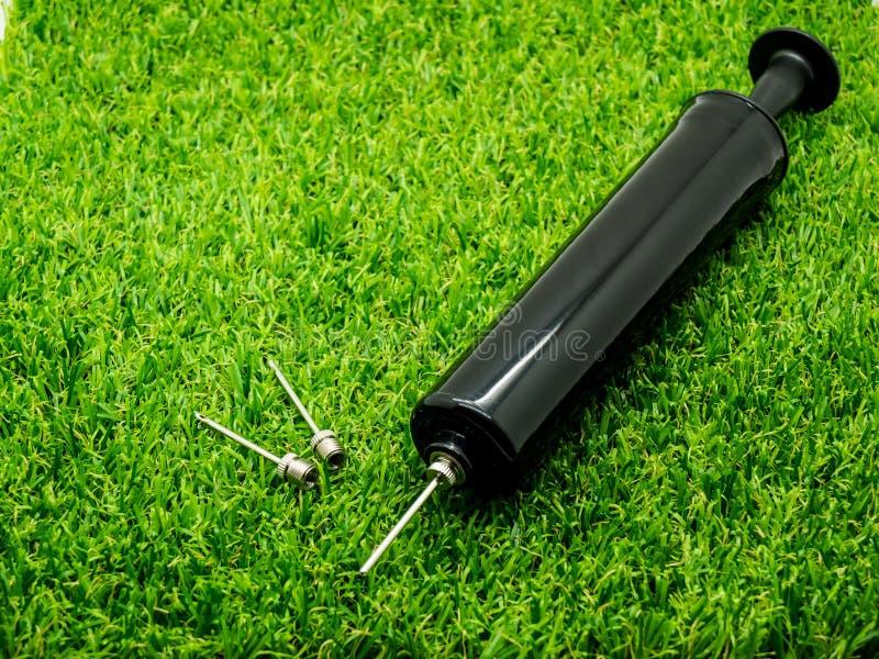 Belägga med metall den inklusive tunga pumpen för inflationvisaren på gräset royaltyfri fotografi