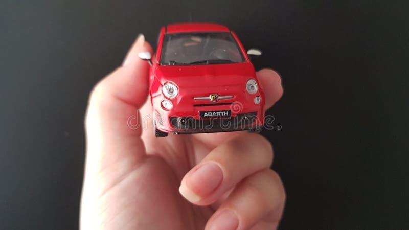 Belägga med metall den lilla Fiat 500 modellen i kvinnlig hand royaltyfri bild