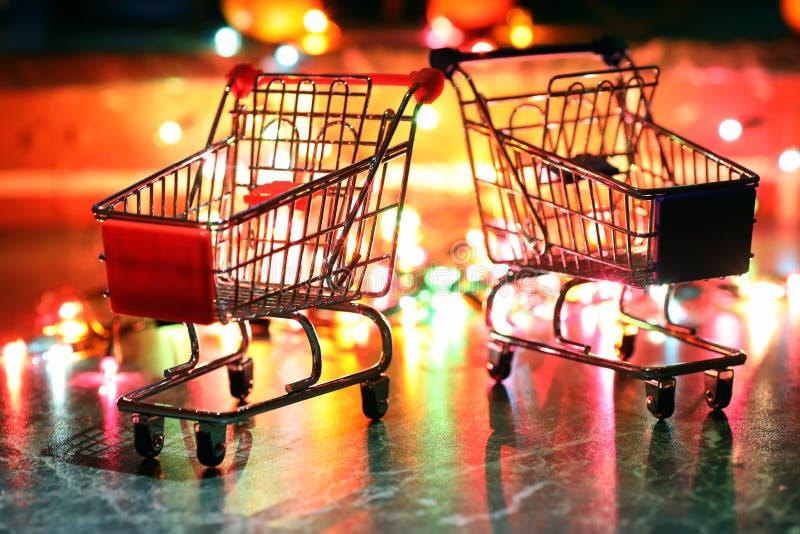 Belägga med metall den lilla vagnen för supermarket på en bakgrund färgade ljus arkivfoton