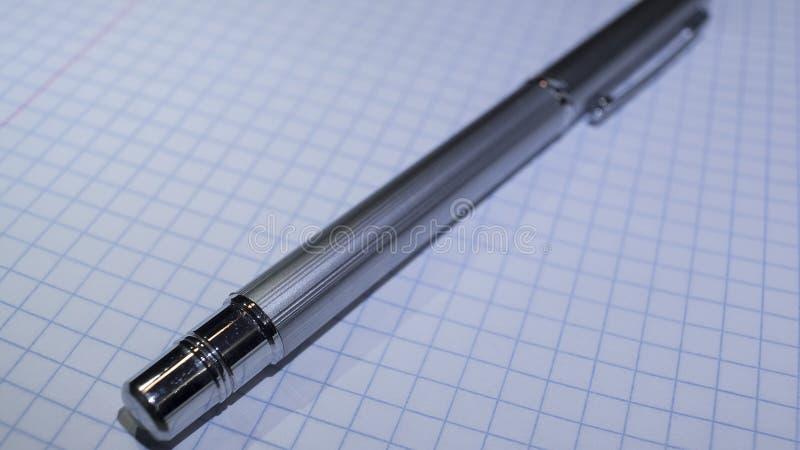Belägga med metall den skinande pennan på en anteckningsbok i asken royaltyfri bild