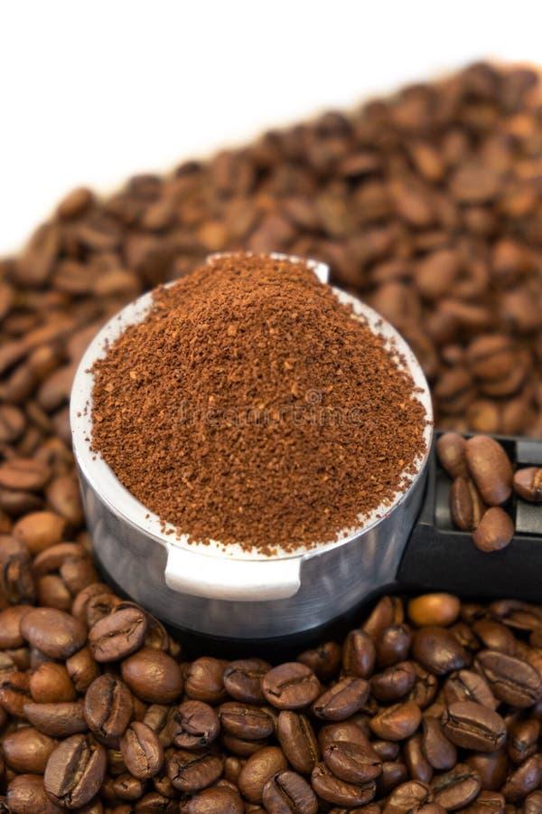 Belägga med metall hållaren med jordkaffe på kaffebönor royaltyfria bilder