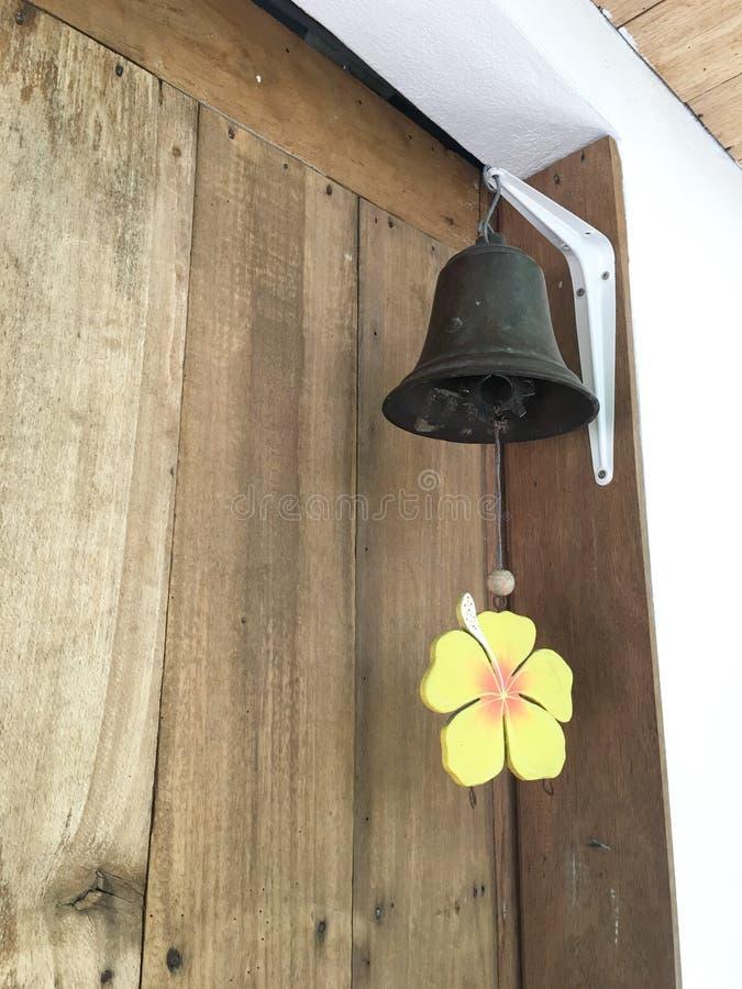 Belägga med metall klockan som hänger på hörnet av trädörren arkivfoto