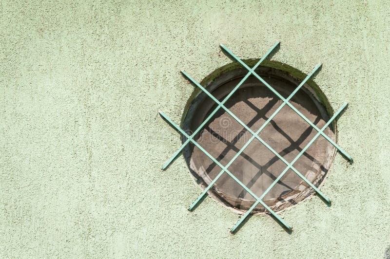 Belägga med metall säkerhetsrastret eller gratings på fönstret från gatasidan för att skydda huset från inbrott royaltyfria bilder