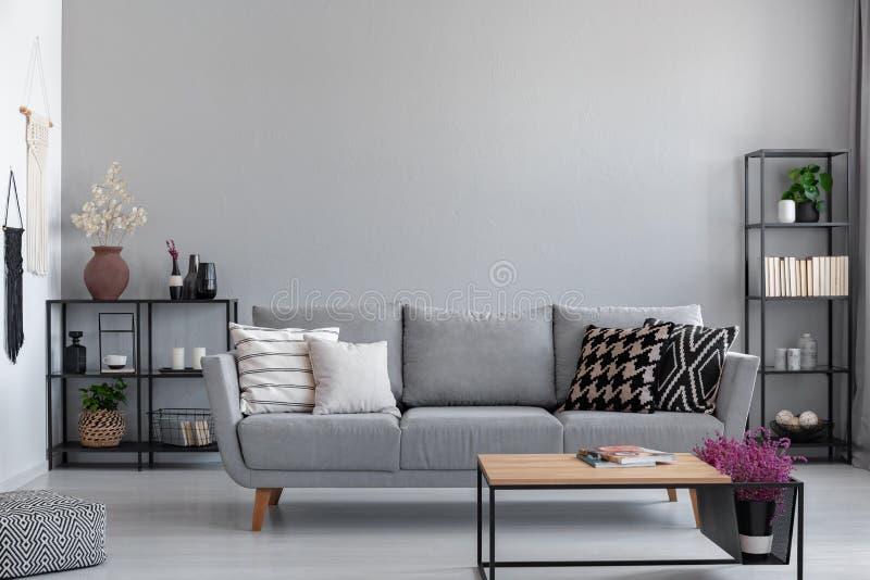 Belägga med metall svarta hyllor med böcker, stearinljus och växter bak den gråa soffan med mönstrade kuddar, verkligt foto med k royaltyfri fotografi