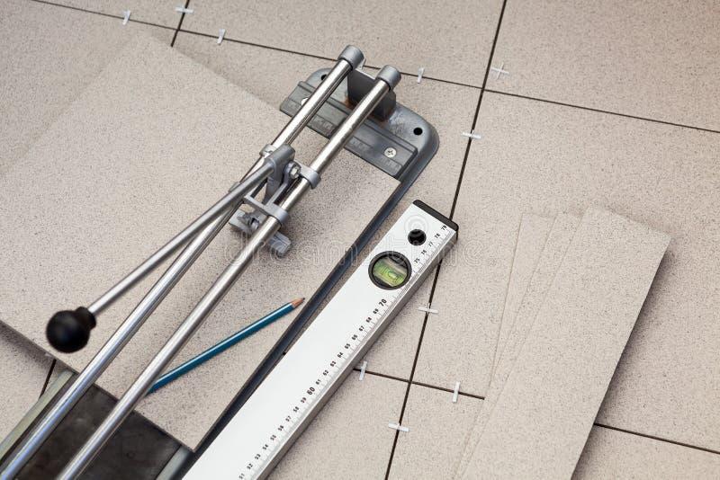 Belägga med tegel att markera förfallen regel, när du klipper med tegelplattaskäraren royaltyfri foto