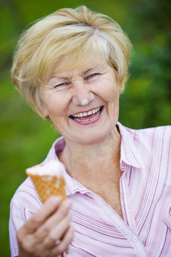 Belåtenhet. Jublande extatisk glass och skratta för gammal kvinna hållande royaltyfri bild