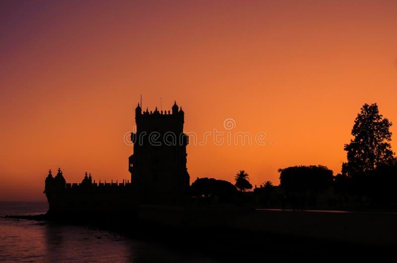 Belém. Belem building in Portugal, brick tower in the sunset. Silhouette. Beautiful orange sky stock image