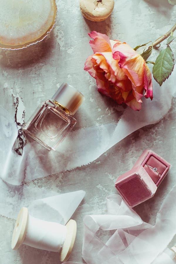 Bel écorcement plat dans des couleurs doucement roses : le parfum, boîte avec l'anneau, s'est levé, ruban de satin, macaron photographie stock