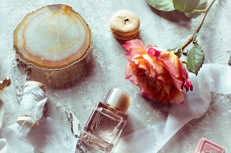Bel écorcement plat dans des couleurs doucement roses : le parfum, boîte avec l'anneau, s'est levé, ruban de satin, macaron photos libres de droits