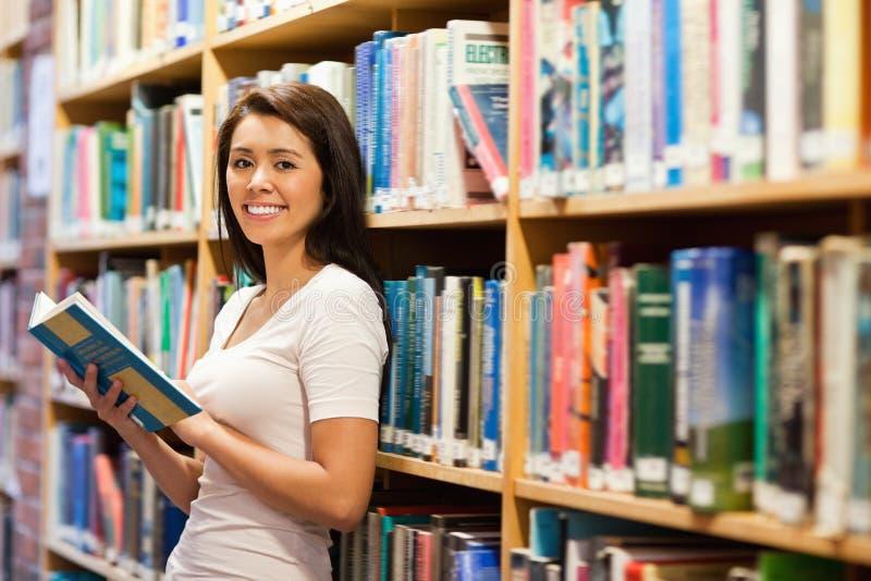 Bel étudiant retenant un livre image libre de droits