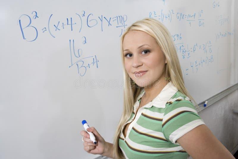 Bel étudiant Solving Algebra Equation sur le tableau blanc image stock