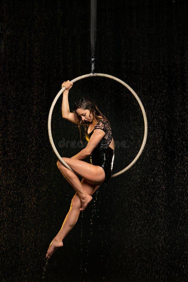 Bel acrobate féminin s'asseyant dans le cercle aérien sous la pluie sur le fond noir photo libre de droits