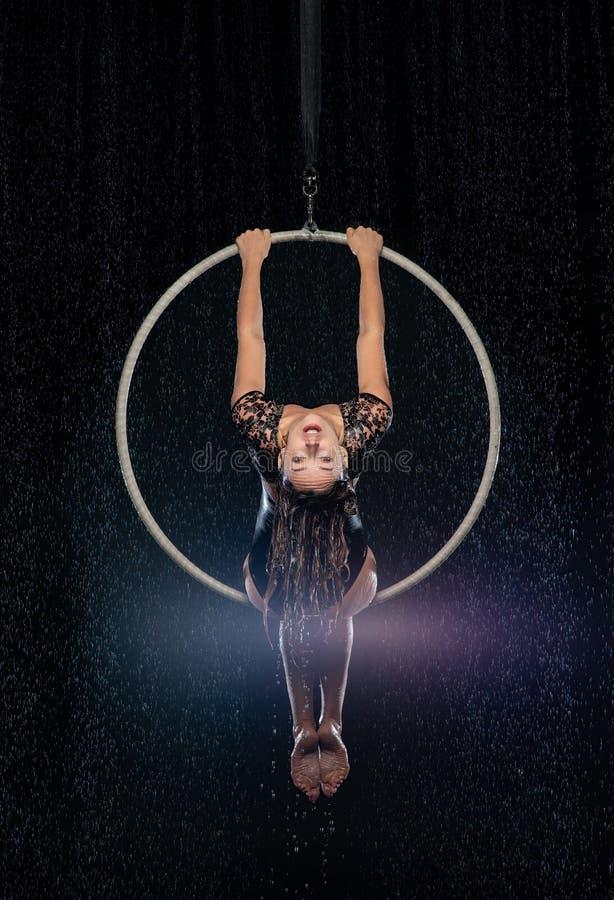 Bel acrobate féminin s'asseyant sur la pose symétrique dans le cercle aérien sous la pluie sur le fond noir photographie stock libre de droits