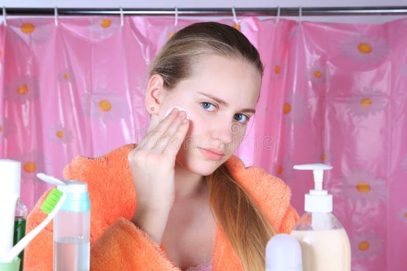 Bel ado de fille dans le nettoyage du visage avec un tampon de coton photographie stock libre de droits