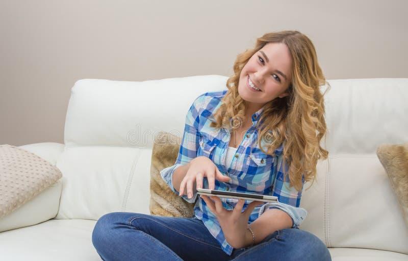 Bel adolescent à l'aide du PC de comprimé se reposant sur le sofa images libres de droits