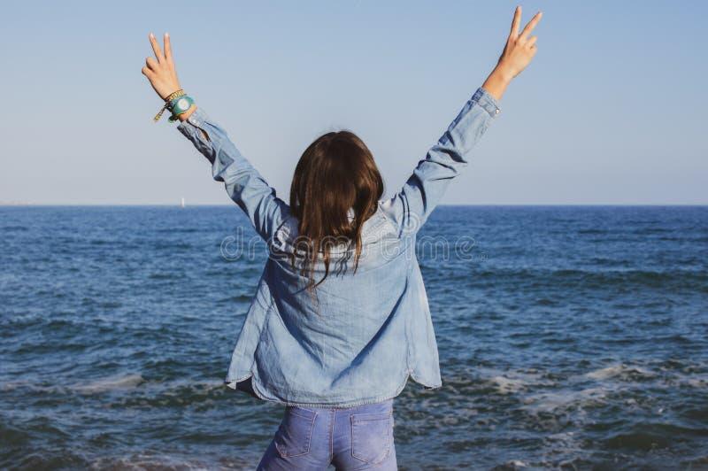Bel adolescent victorieux devant la mer Méditerranée avec des bras augmentés images libres de droits