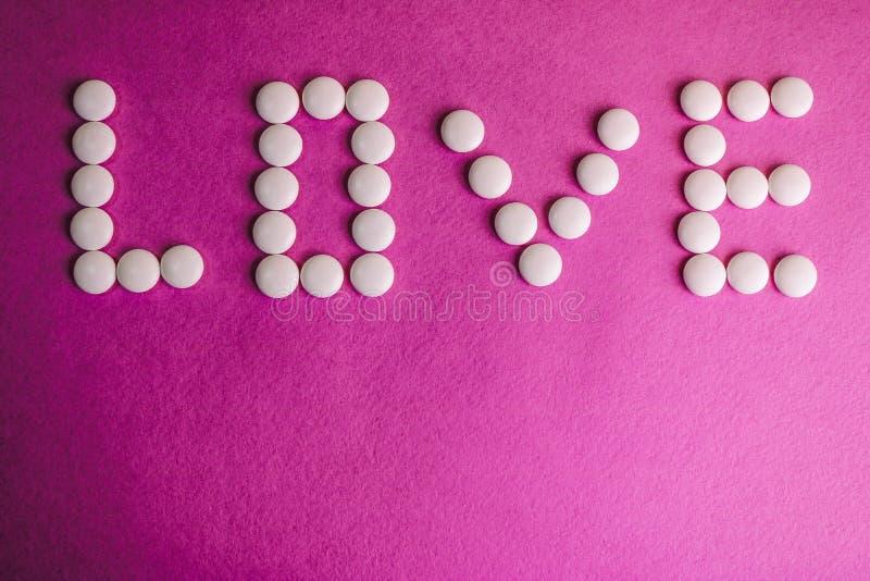 Bel amour d'inscription fait à partir des pilules de rond blanc, des vitamines, des antibiotiques et de l'espace médicaux doux de images stock
