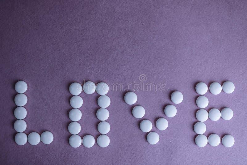 Bel amour d'inscription fait à partir des pilules de rond blanc, des vitamines, des antibiotiques et de l'espace médicaux doux de photographie stock libre de droits