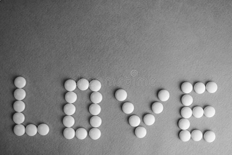Bel amour d'inscription fait à partir des pilules de rond blanc, des vitamines, des antibiotiques et de l'espace médicaux doux de photographie stock