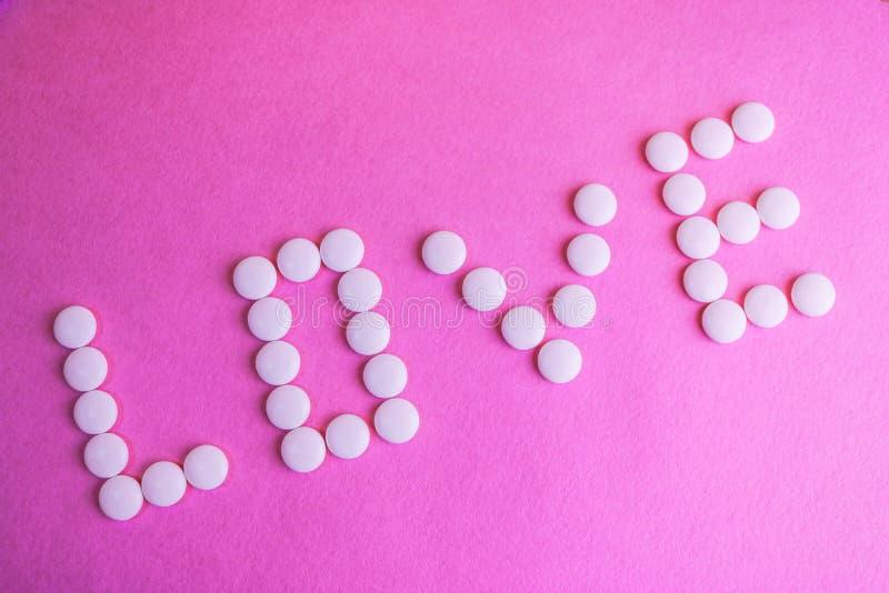 Bel amour d'inscription fait à partir des pilules de rond blanc, des vitamines, des antibiotiques et de l'espace médicaux doux de images libres de droits