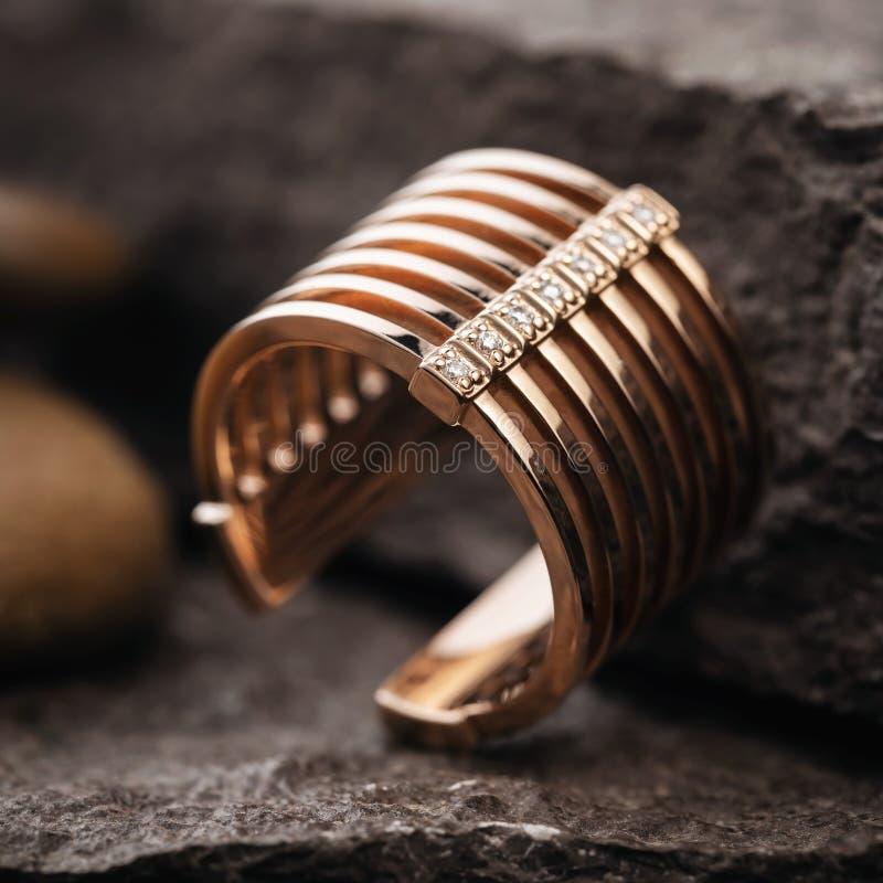 Bel anneau d'or femelle orné avec de petites gemmes de divers côtés sur une surface en pierre images stock