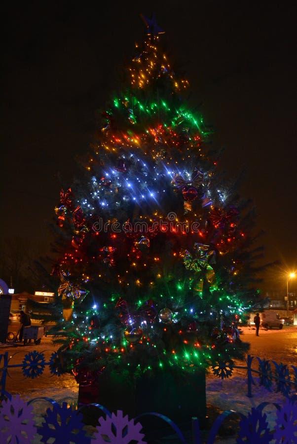 Bel arbre de Noël, pin naturel avec les ampoules rouges, bleues, vertes et jaunes de LED, belles boules, jouets Les vacances de n photographie stock