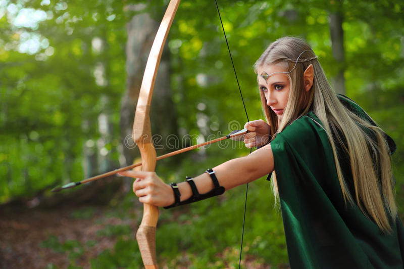 Bel archer féminin d'elfe dans la chasse de forêt avec un arc images stock