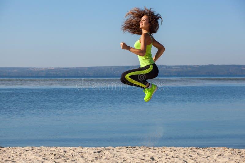 Bel athlète attirant sautant pendant les sports sur la plage pendant le matin photos stock