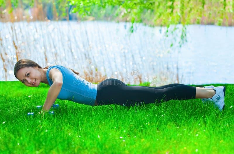 Bel athlète de femme impliqué dans les sports sur la rue, en parc, formation de conduite des haltères dans des ses mains photos stock