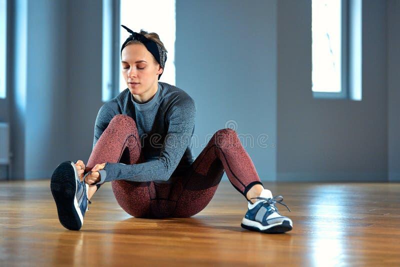 Bel athlète de jeune femme attachant des dentelles sur des espadrilles tout en détendant de la formation de force dans le gymnase photo libre de droits