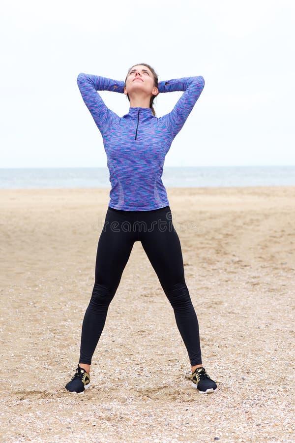 Bel athlète féminin faisant le yoga sur la plage photographie stock