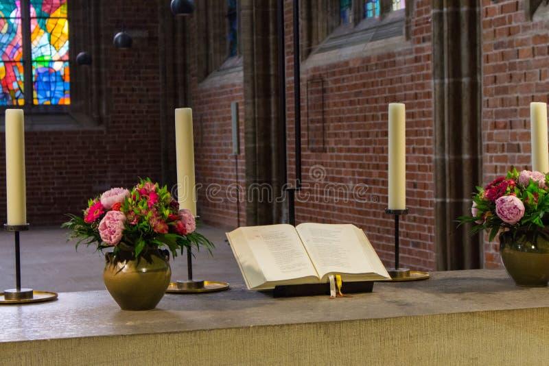 Bel autel dans la cathédrale catholique Sainte Bible ouverte avec des fleurs, des bougies et la croix Décoration élégante d'églis image libre de droits