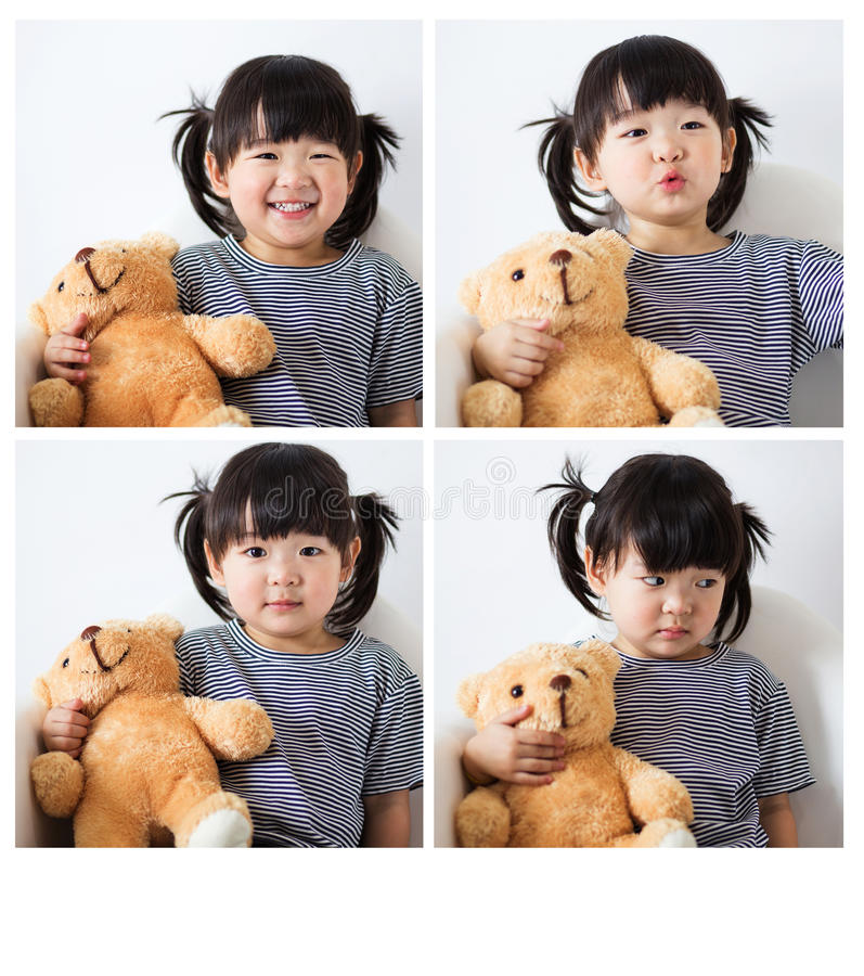 Bel enfant asiatique préscolaire avec des positions de la pose quatre de grève de nounours image stock