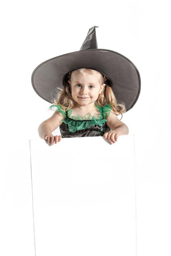 Bel enfant dans le costume de sorcière de Halloween avec le chapeau tenant un conseil vide pour la publicité photographie stock libre de droits