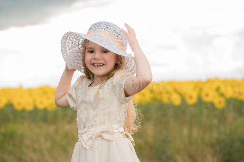 Bel enfant dans un chapeau sur le champ avec des fleurs photos stock