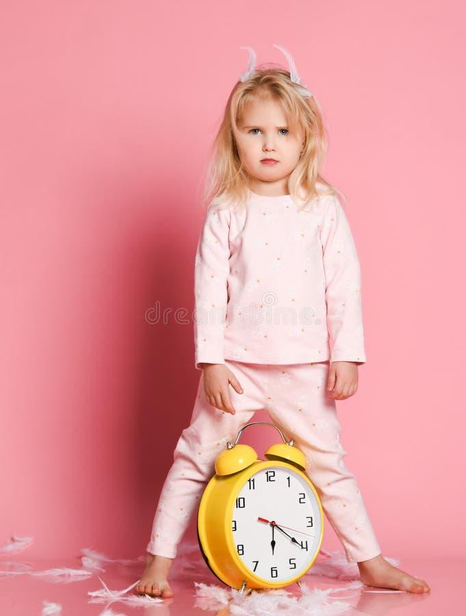 Bel enfant en bas âge blond jouant avec le réveil photos libres de droits
