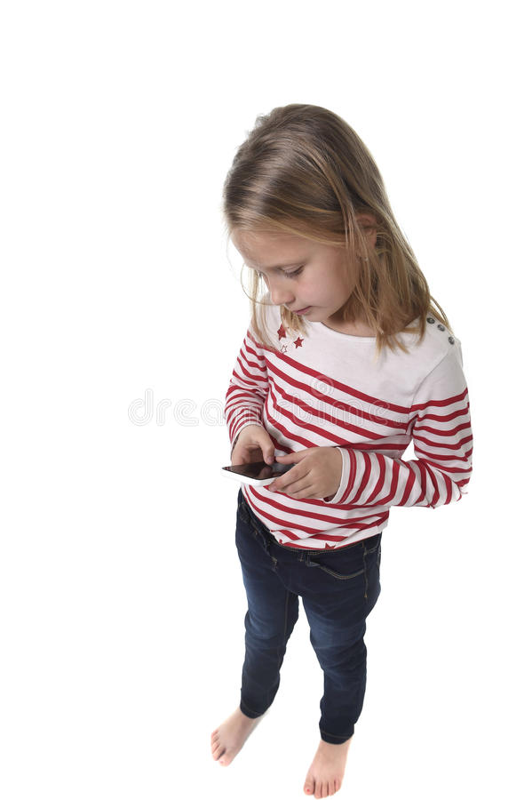 Bel enfant féminin avec les cheveux blonds et les yeux bleus utilisant le téléphone portable jouant le jeu photos stock