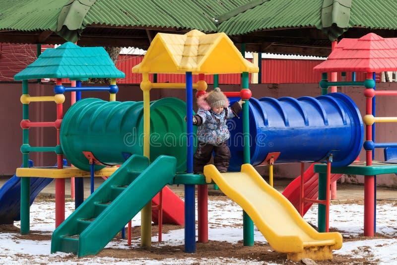 Bel enfant heureux sur un terrain de jeu d'hiver extérieur photos libres de droits