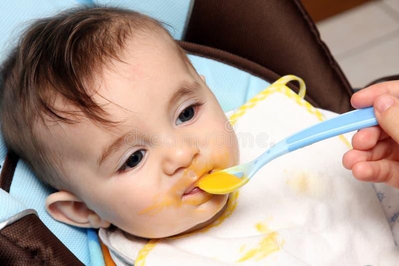 Bel enfant mangeant du potage photo stock
