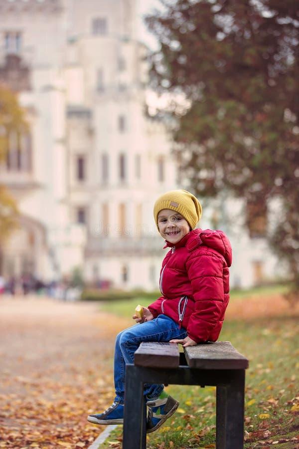 Bel enfant mignon, garçon, s'asseyant sur un banc devant le beauti images libres de droits