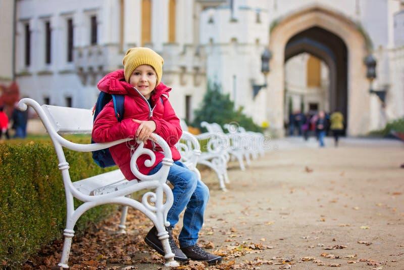 Bel enfant mignon, garçon, s'asseyant sur un banc devant le beauti photo stock