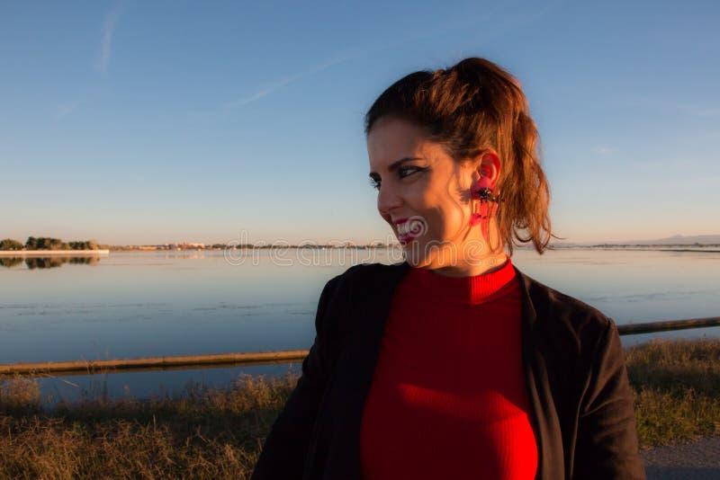 Bel ext?rieur de position de portrait de femme de brune dans un jour ensoleill?, avec un lac ? l'arri?re-plan images stock