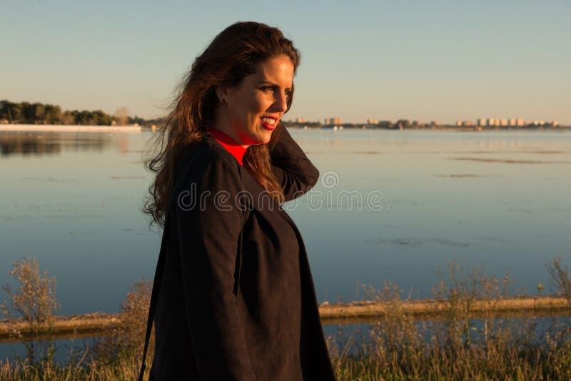 Bel ext?rieur de position de portrait de femme de brune dans un jour ensoleill?, avec un lac ? l'arri?re-plan photos libres de droits