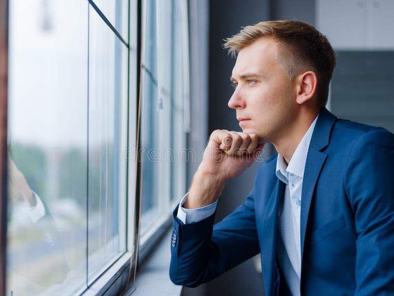 Bel homme d'affaires regardant dans la fenêtre sur un fond brouillé Concept d'affaires Copiez l'espace photos libres de droits