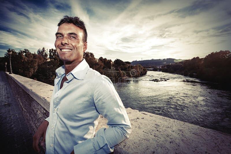 Bel homme italien de sourire dehors à Rome Italie Rivière du Tibre du pont images libres de droits