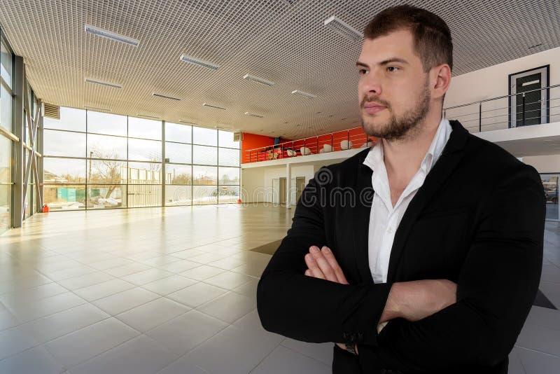 Bel homme sérieux d'affaires sur le fond central de revendeur vide photo libre de droits